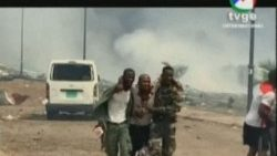 Screenshot of TVGE shows soldiers assisting a wounded man in Bata, as smoke rises in the background