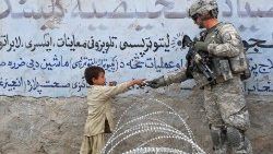 File photo: A US soldier hands an Afghan child a gift in Langarhar in 2010