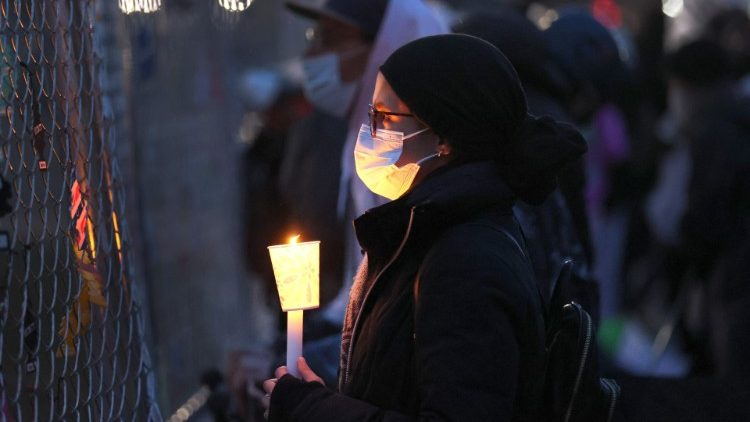 A woman holds a candle at a vigil outside a police station near Minneapolis