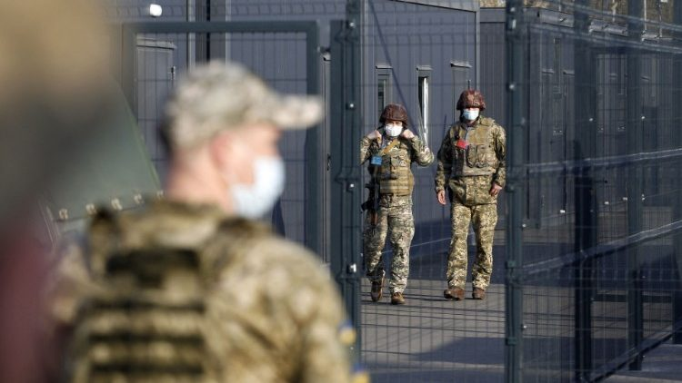 A Ukrainian soldier stands guard at a checkpoint with Russian-backed separatists in the Lugansk region.