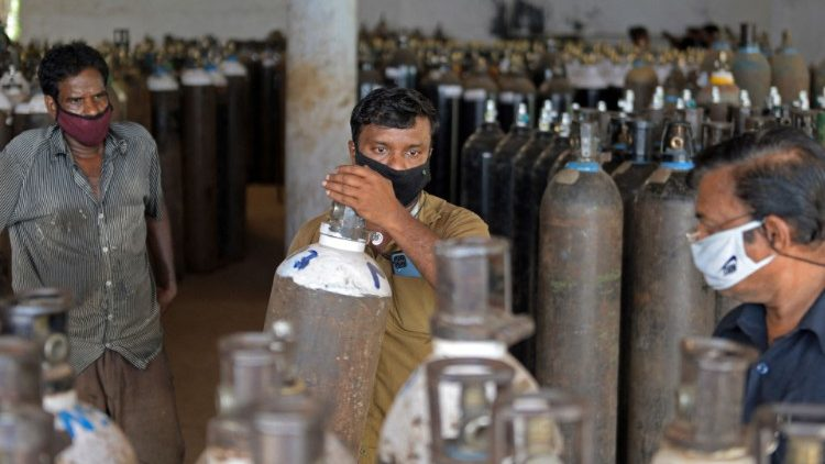 Workers arrange supplies of oxygen to be transported to hospitals in India