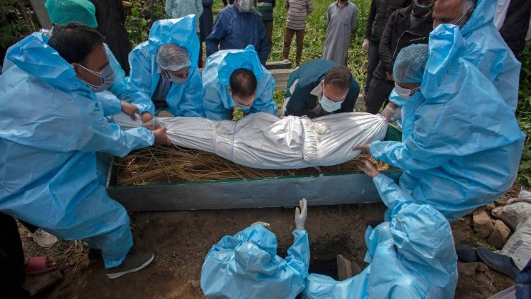 Relatives in protective gear bury a victim who died of Covid-19.