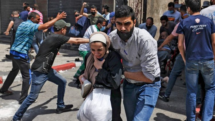 Palestinians evacuate a building targeted by Israeli bombardment in Gaza City on 11 May 2021