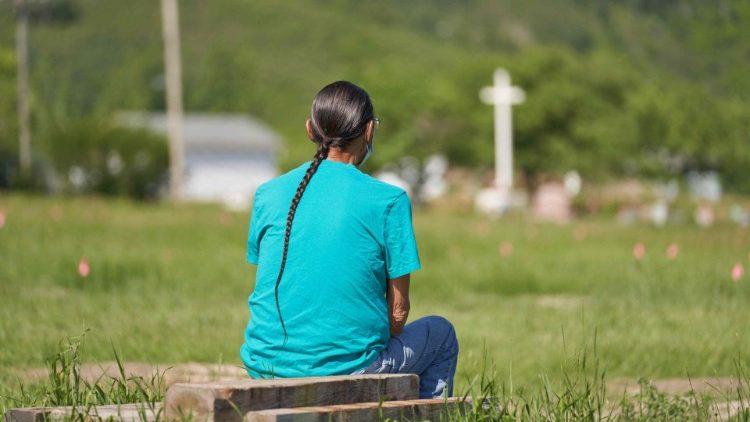 Một Người Bản địa Canada cầu nguyện tại cánh đồng nơi tìm thấy hài cốt của 750 học sinh nội trú