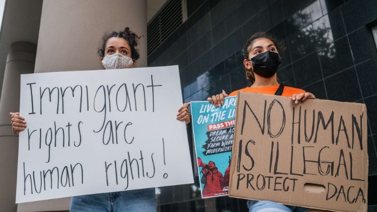 People hold placards at a rally at U.S. District Court in support of DACA applicants