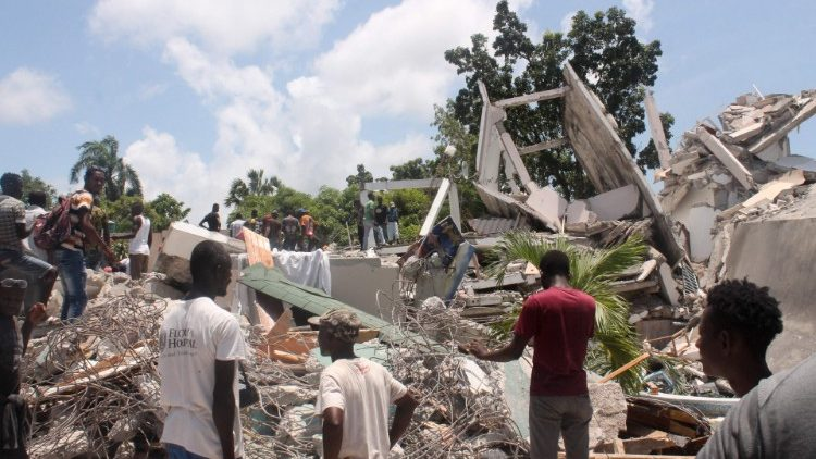 People search through the rubble of a building in Les Cayes, Haiti