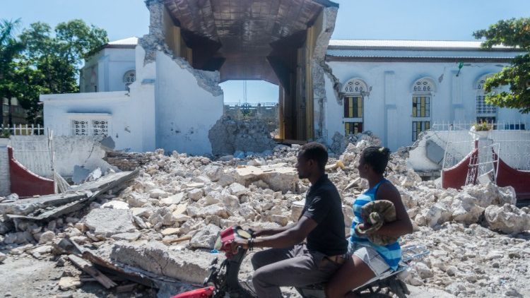 """People pass in front of the rubble from a destroyed wall outside of the """"Sacre Coeur de Cayes"""" church in Les Cayes"""
