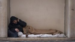 A homeless man sleeps outside in Rome during freezing weather