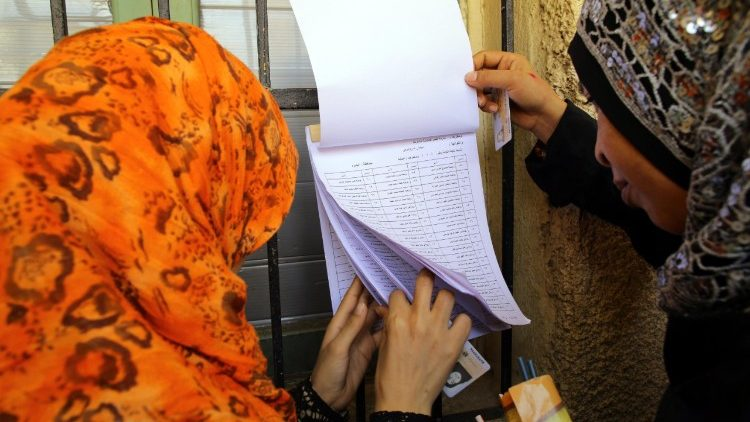Egyptian women check their names at a polling station during day one of the presidential election in Cairo