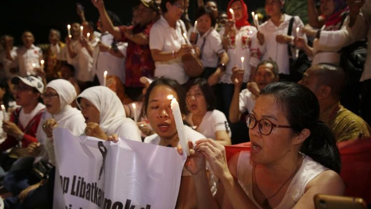 Indonesian activists hold a candle-lit vigil for victims of suicide bomb attacks in Surabaya.
