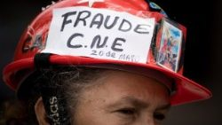Reacting to Venezuela election, protester wears helmit reading 'Fraud'