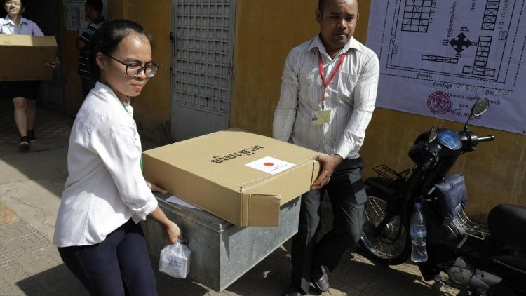 Election officials carry election materials in preparation for Cambodia's July 28 general elections.