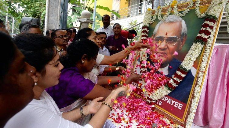 Indians paying homage to a portrait of late Atal Bihari Vajpayee.
