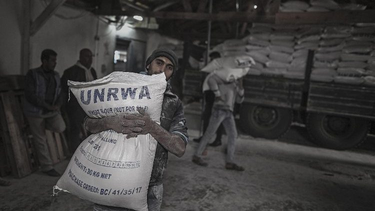 This file photo shows a Palestinian refugee carrying a UNRWA sack of flour