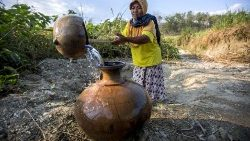 A villager collects water from a well during a drought in Indonesia