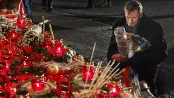 A Ukrainian man kneels before a Holodomor memorial in Kiev