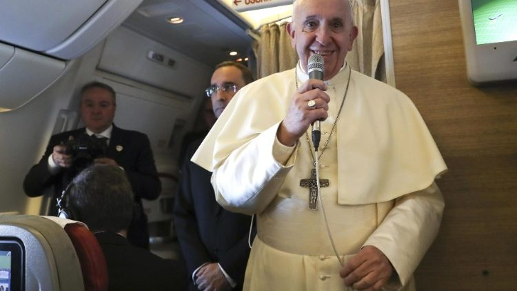 Pope Francis speaks to reporters aboard a plane