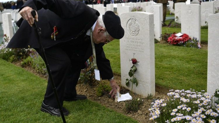 A WWII veteran lays a message at a fallen soldier's grave in Bayeux, France