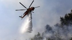 A helicopter drops water over a forest fire on Evia