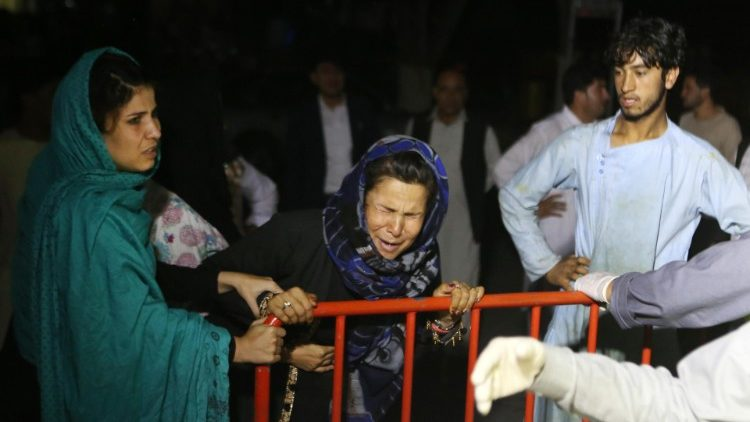 An Afghan woman grieves over the loss of her husband and 2 sons