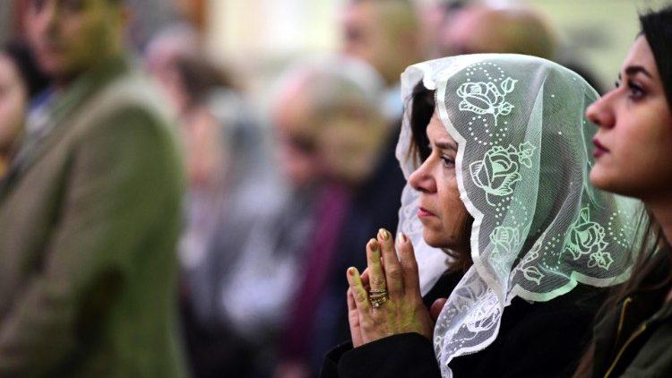 Des chrétiennes irakiennes en prière dans une église de Bagdad lors de la messe de Noël, en 2019.