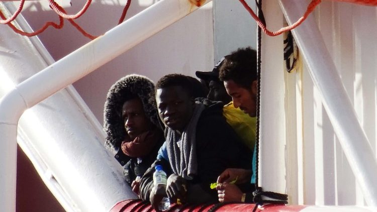 North African migrants waiting to disembark from a rescue vessel in the southern Italian city of Taranto