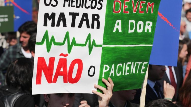 "A demonstrater holds up a sign reading ""Doctors should kill pain, not the patient"" during a protest last year against efforts to legalize euthanasia in Portugal"