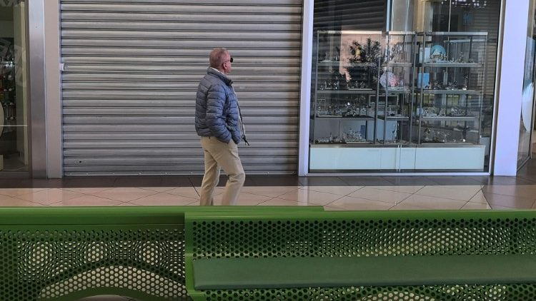 A man walks past closed shops in a mall in Padua