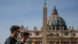Tourists pass in front of St Peter's Basilica wearing masks