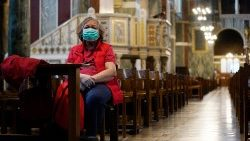 A worshipper wearing a face mask in an empty Westminster Cathedral