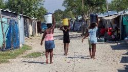 Women carry the water collected from La Piste camp in Port-au-Prince, Haiti