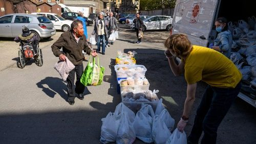 Members of Caritas give out food the homeless and needy