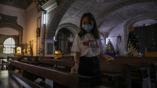 A volunteer puts social-distancing markers on a pew in a Manila church