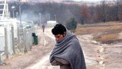 A migrant tries to warm himself at the Lipa camp in Bihac, Boznia and Herzegovina, 1 January 2021