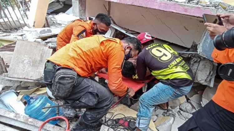 Rescuers pulling a survivor out of the rubble of a collapsed building in West Sulawesi following a 6.2 magnitude earthquake  on 15 January 2021