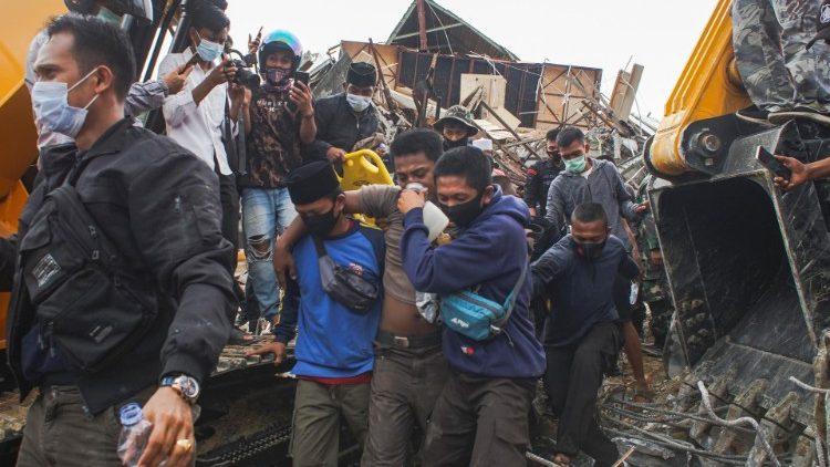 Rescuers evacuate a survivor in Mamuju, West Sulawesi