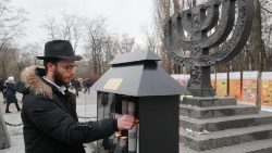 A man lights a candle during a ceremony marking Holocaust Remembrance Day
