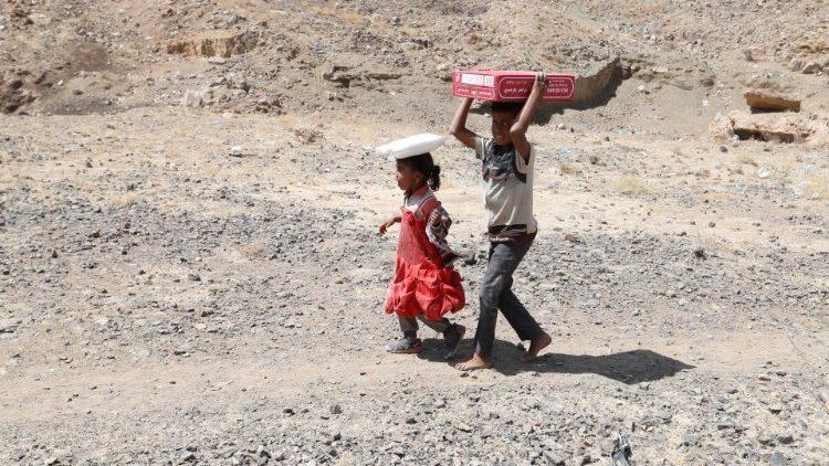 Los pequeños desplazados yemeníes ayudan a llevar  raciones de comida
