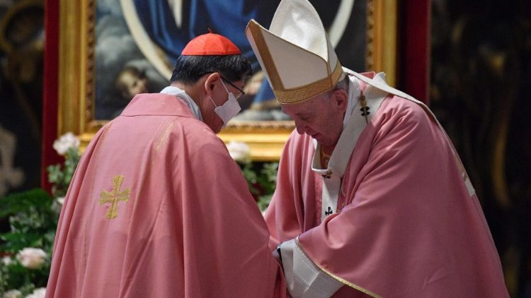 Pope Francis speaks to Cardinal Luis Antonio Tagle after Mass in St. Peter's