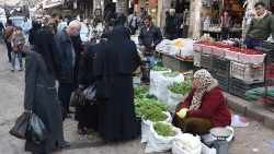 Syrians shop at a market in Damascus, as the nations marks 10 years of war
