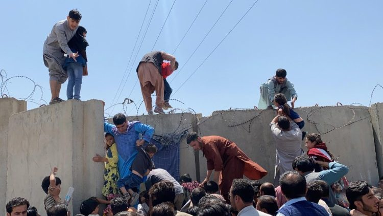 People struggling to cross the boundary wall at Kabul's international airport as the Taliban takes control of the city