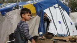 children-look-on-at-a-makeshift-camp-next-to--1543589347917.JPG