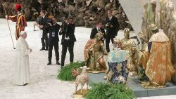 Pope Francis prays in front of the nativity scene during the general audience at the Paul VI Hall in Vatican