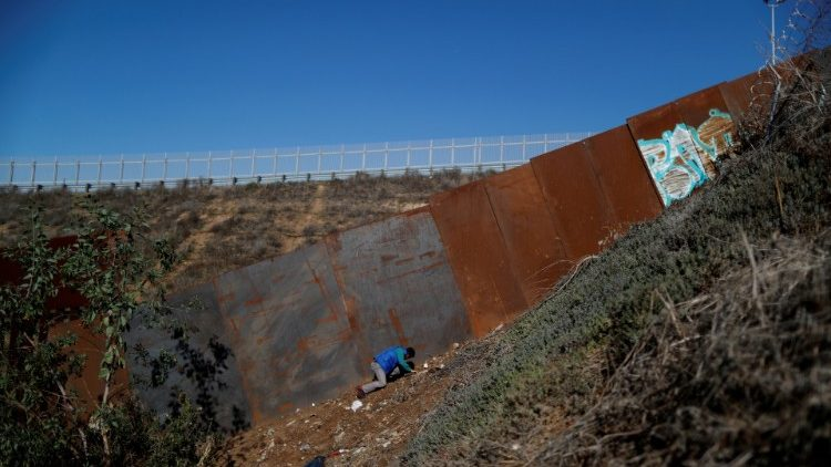 A migrant, who is part of a caravan of thousands from Central America trying to reach the United States, looks at a hole under the border wall as he tries to cross from Mexico to the U.S in Tijuana