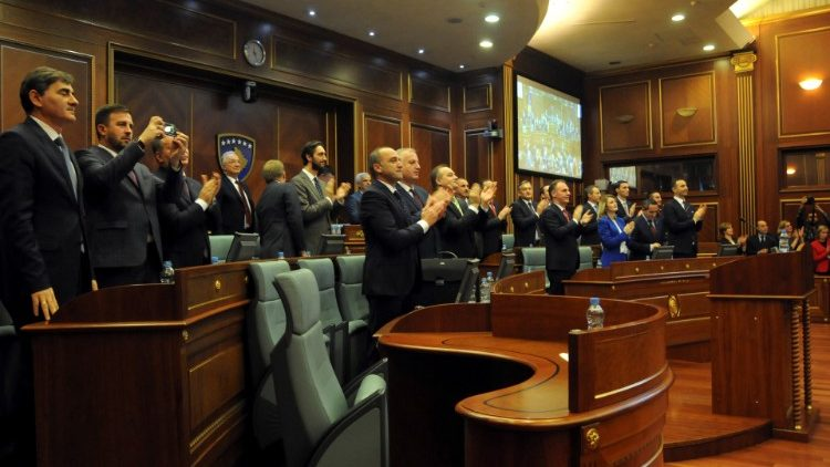 Kosovo's lawmakers applaud after approving the formation of a national army
