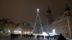 People walk near a Christmas tree in front of the Royal Castle in Warsaw