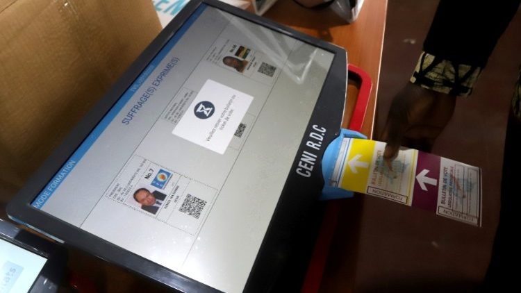 A worker of Congo's National Independent Electoral Commission (CENI), tests a voting machine ahead of the postponed presidential election, at the CENI offices in Kinshasa