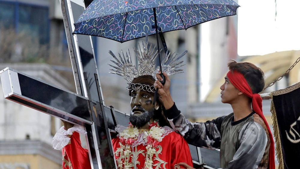 A devotee shelters a replica of Black Nazarene from the drizzle during a parade, two days before the annual procession to celebrate its feast day in Quiapo, Manila