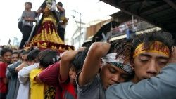 Devotees pull a chariot as they parade a replica of the Black Nazarene, two days before the annual procession to celebrate its feast day in Quiapo, Manila