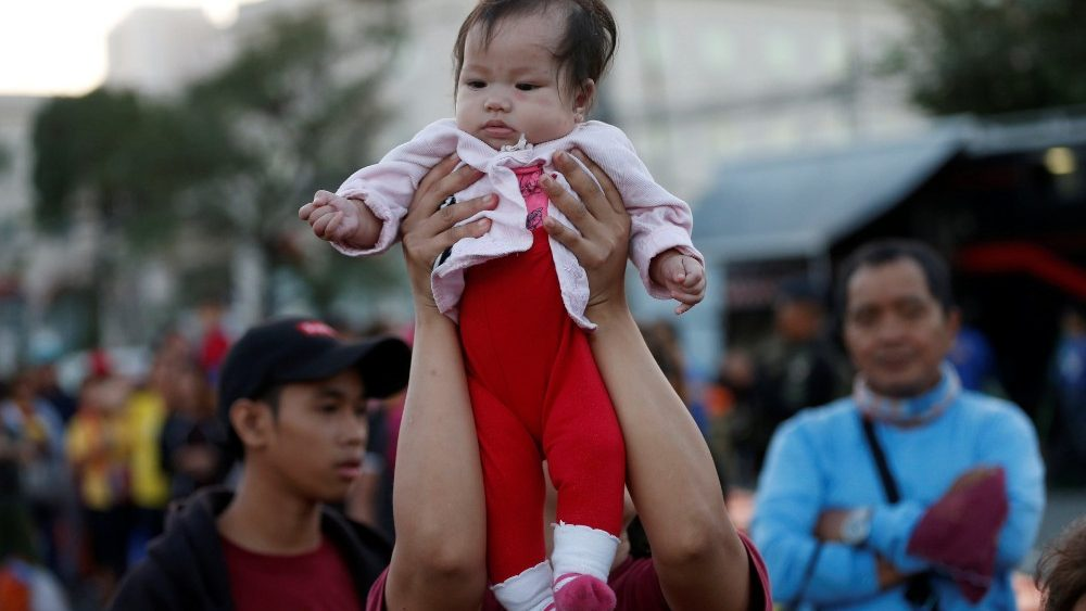 A child is held up by her mother as devotees wait in line one day before the annual Black Nazarene procession, to touch the image, in Quiapo